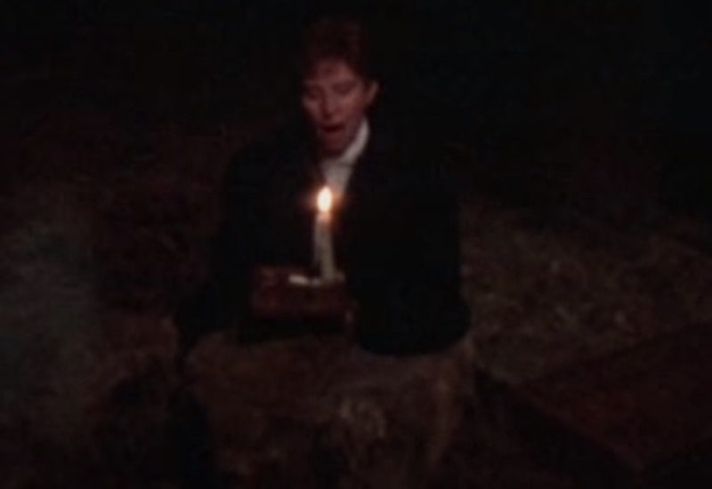 Barbra Streisand, dressed as the male character Anshel, holds a candle in a still from the film Yentl
